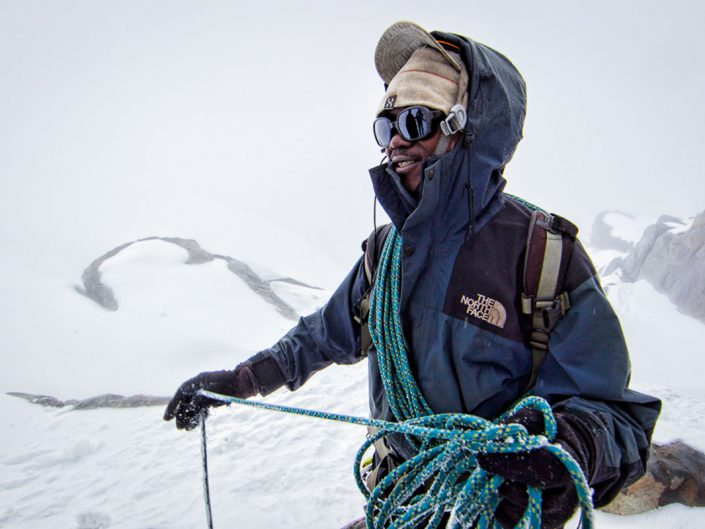 Day 6 Kilembe Route summit day, climbing back down from Margherita Peak, guide Benard Enaga straightens up the ropes